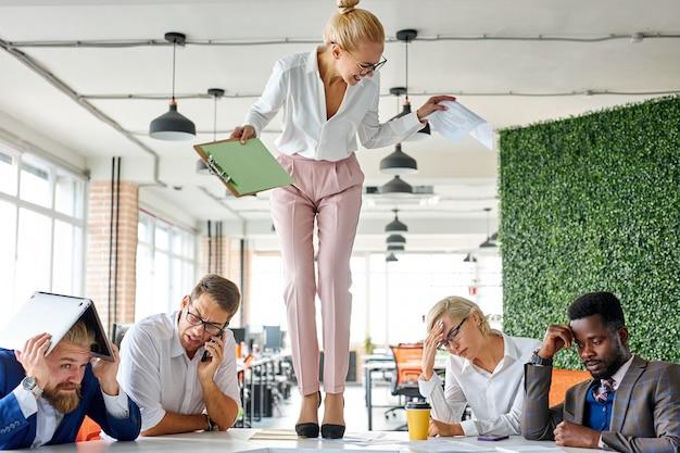 怒りのアンバランスな女性上司が叫び、職場の計画を果たせなかったことで従業員を叱る Premium写真