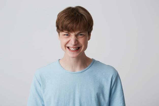 Adolescente arrabbiato, sconvolto, irato scopre i denti mostrando le parentesi graffe Foto Gratuite