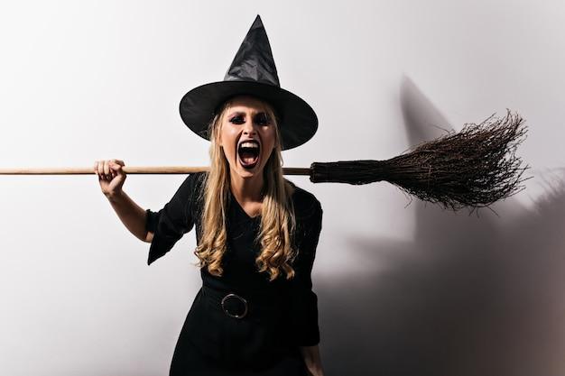 Злая ведьма с длинными волосами, держащая метлу. блондинка женский волшебник кричит в хэллоуин. Бесплатные Фотографии