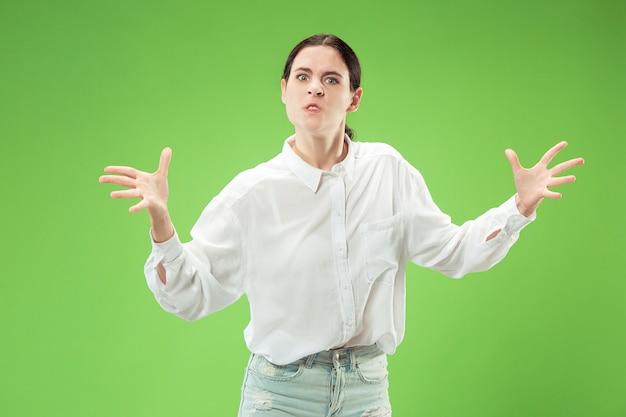 カメラを見ている怒っている女性。トレンディな緑のスタジオの背景に孤立して立っている積極的なビジネス女性。女性の半身像。 無料写真