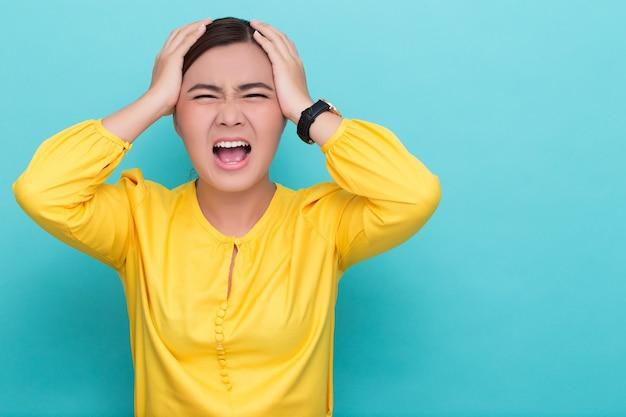 叫んで、髪を引っ張って怒っている女性 Premium写真