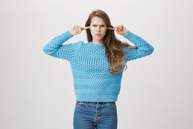 Сердитая женщина закрыла уши пальцами Бесплатные Фотографии