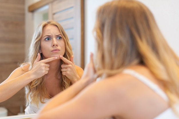 Angry woman squeezing pimple from face Free Photo