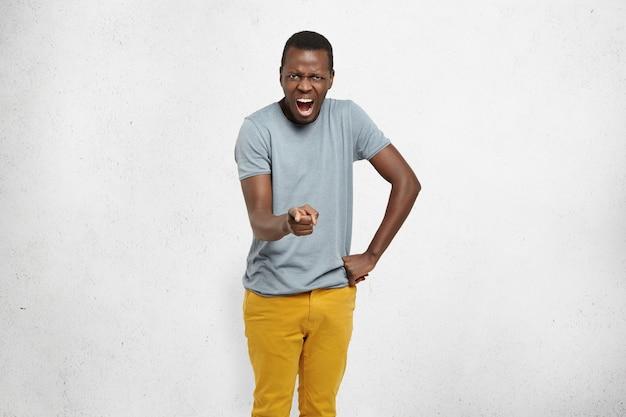 Arrabbiato giovane cliente afro-americano che punta il dito indice alla telecamera Foto Gratuite
