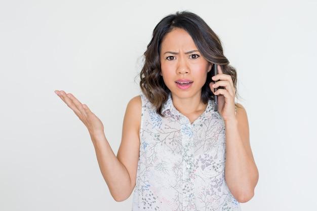 電話で話す怒っている若いアジア人女性 Premium写真