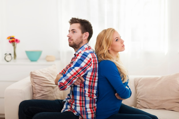 Angry young couple sitting back to back at home Free Photo
