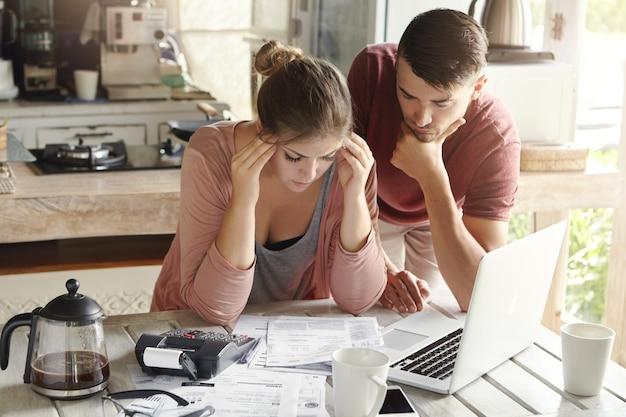 Giovane donna arrabbiata che si sente depressa, stringendo le tempie, cercando di risolvere i problemi finanziari Foto Gratuite
