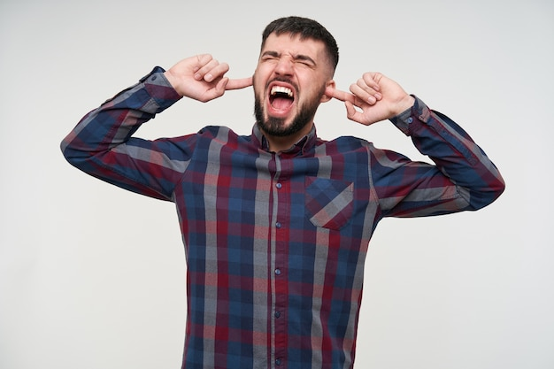 Angry young handsome dark haired bearded male with short haircut covering his ears and screaming loud with wide mouth opened, being annoyed because of loud sounds, isolated over white wall Free Photo