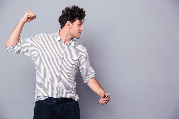 彼の拳を握りしめている怒っている若い男 Premium写真