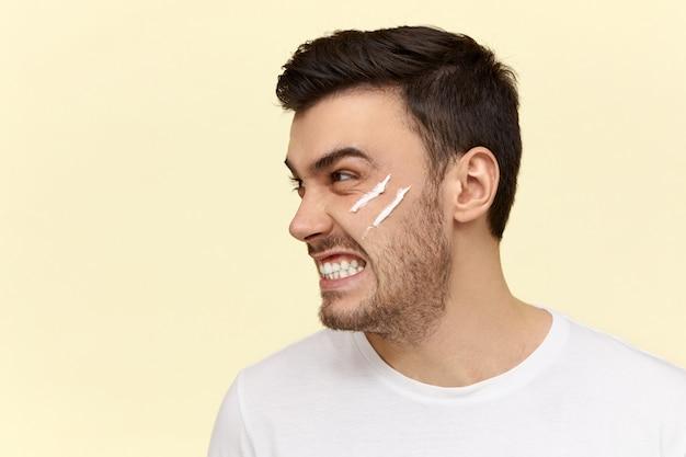 Злой молодой человек делает утреннюю рутину с кремом-лосьоном на лице Бесплатные Фотографии