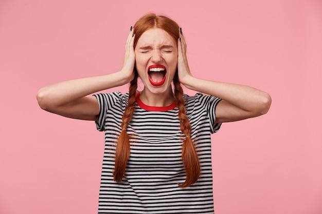 Giovane ragazza dai capelli rossi arrabbiata in maglietta spogliata, tiene gli occhi chiusi, chiude le orecchie con i palmi delle mani, mostra il gesto di ignorare, dimostra un forte urlo o grida, oltre il muro rosa Foto Gratuite