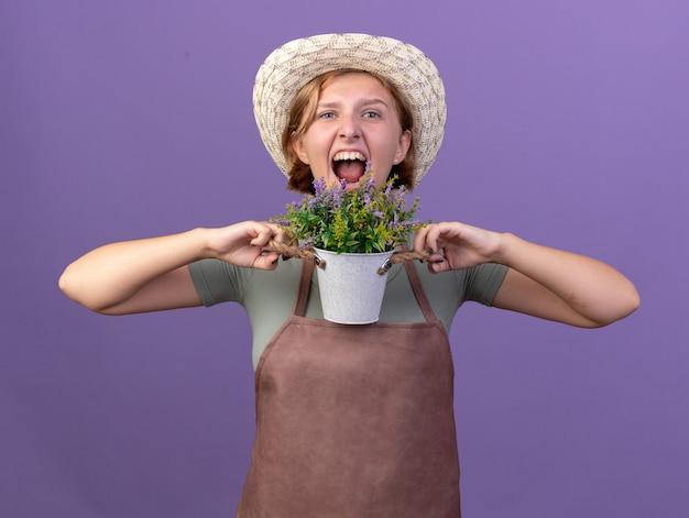 コピースペースと紫色の壁に分離された植木鉢に花を保持しているガーデニング帽子をかぶって怒っている若いスラブ女性庭師 無料写真