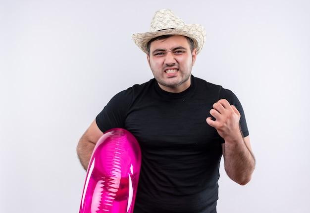 Сердитый молодой путешественник в черной футболке и летней шляпе держит надувное кольцо с раздраженным выражением лица, стоящий над белой стеной Бесплатные Фотографии