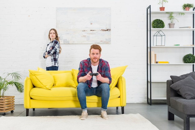 An angry young woman standing behind the yellow sofa with her boyfriend playing the video game Free Photo