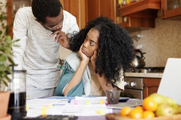 Giovane donna arrabbiata con taglio di capelli afro guardando il marito con disappunto durante la lite sui debiti a casa, seduto al tavolo della cucina con un sacco di carte e laptop. concetto di problemi finanziari Foto Gratuite