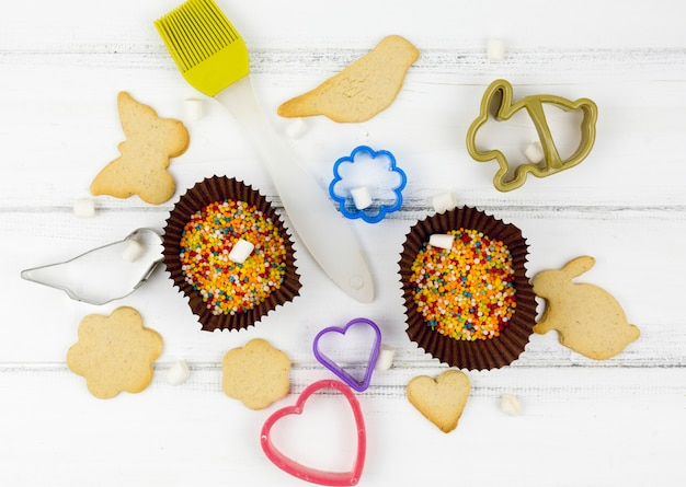Animal shaped cookies with kitchen utensils on white table Free Photo