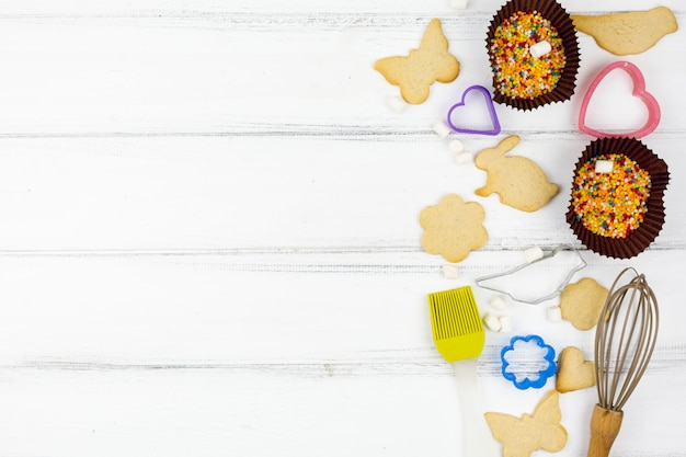 Animal shaped cookies with kitchen utensils on wooden table Free Photo