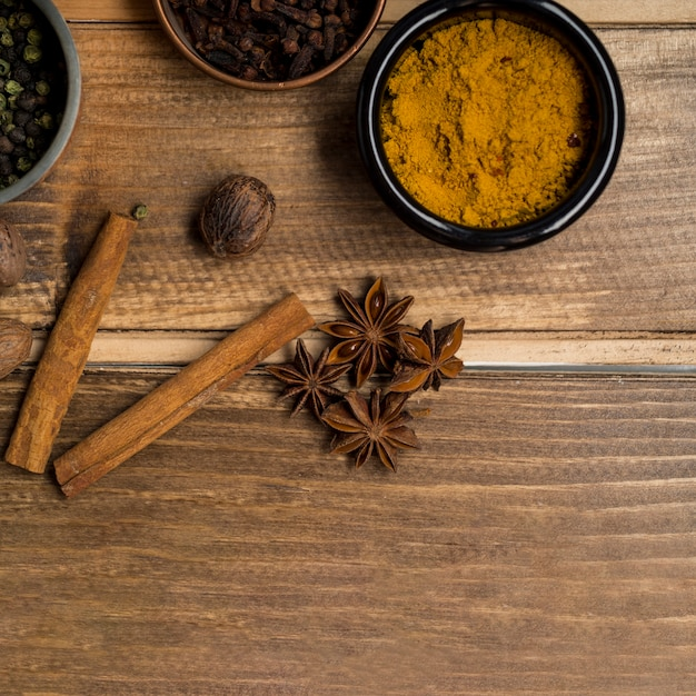Anise and cinnamon near bowls with spices Free Photo