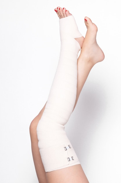 Ankle woman on a white background dragged elastic bandage Premium Photo