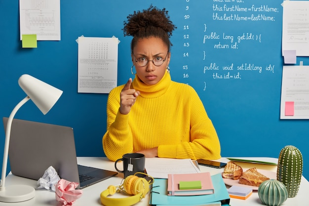 La lavoratrice afroamericana infastidita ti indica e incolpa di aver fatto qualcosa di sbagliato, indossa occhiali rotondi e maglione giallo, siede in uno spazio di lavoro con il disordine sul tavolo. Foto Gratuite