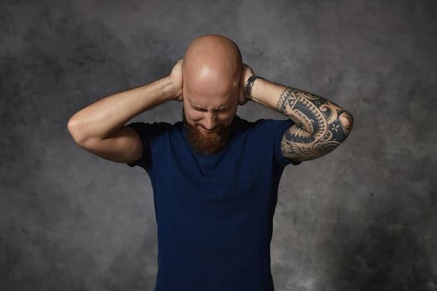 Ragazzo calvo arrabbiato infastidito con tatuaggio che chiude gli occhi e copre le orecchie con le mani, non sopporta le urla della sua moglie furiosa mentre litiga. linguaggio del corpo ed emozioni umane Foto Gratuite