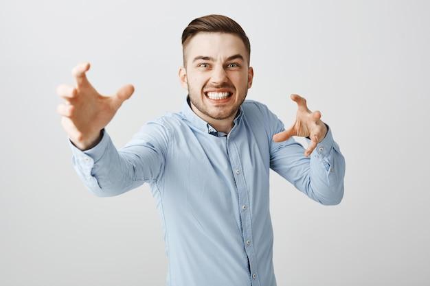 L'uomo d'affari infastidito sembra arrabbiato raggiungendo le mani in avanti per strangolare qualcuno Foto Gratuite
