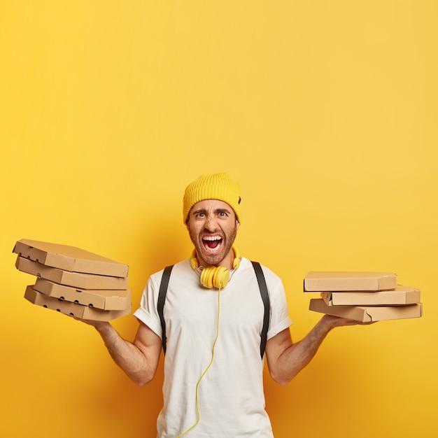 イライラした配達員は、ピザが入ったカートンボックスをたくさん運び、イライラして叫び、同時に多くの仕事をし、クライアントから多くの注文を受けます 無料写真