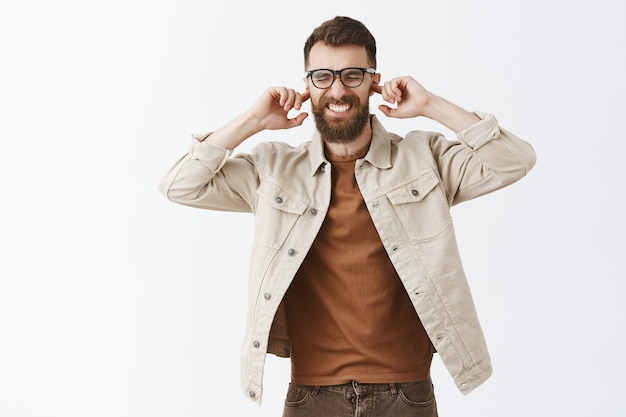 Annoyed and disappointed bearded man in glasses posing against the white wall Free Photo