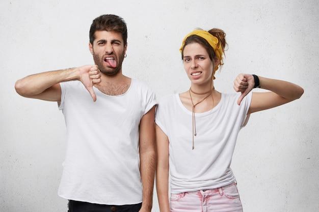 Giovane coppia europea infastidita e disgustata che indossa abiti eleganti che esprimono antipatia, disapprovazione, mancanza di rispetto o disprezzo con gesti, mostrando il pollice verso il basso e facendo smorfie Foto Gratuite