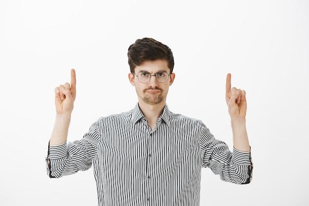 口ひげとあごひげを丸めたメガネで、人差し指を上げ、失望した気になる顔で上向きに悩まされる不快な魅力的な男性モデル 無料写真