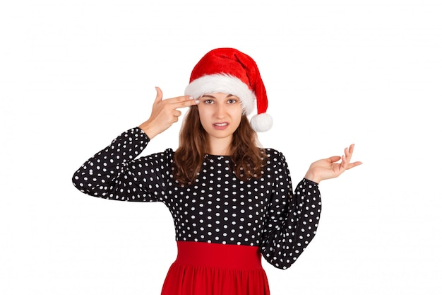 Annoyed and displeased woman in dress shrugging and holding fingers on temple. emotional girl in santa claus christmas hat isolated on white . holiday Premium Photo