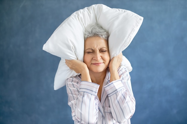 Annoyed dissatisfied mature woman with gray hair grimacing having sleepless night because of loud music Free Photo