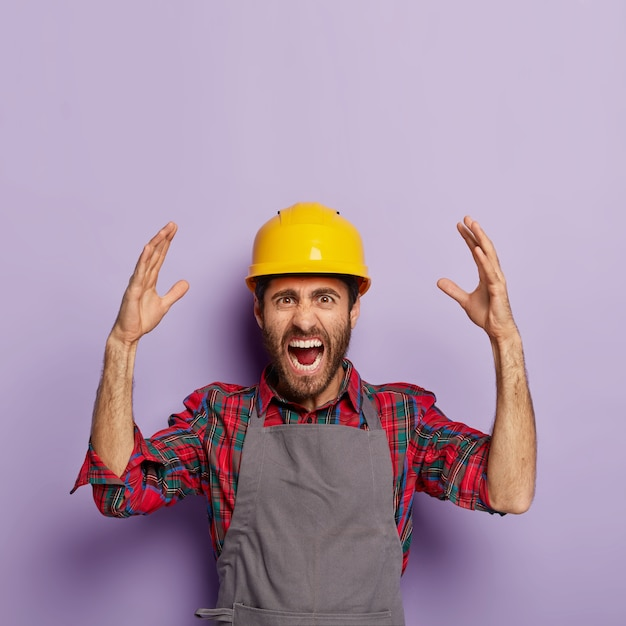 Раздраженный эмоциональный рабочий носит желтый защитный строительный шлем, клетчатую рубашку и фартук, у него много работы, он кричит от стресса и паники, эмоционально поднимает руки Бесплатные Фотографии