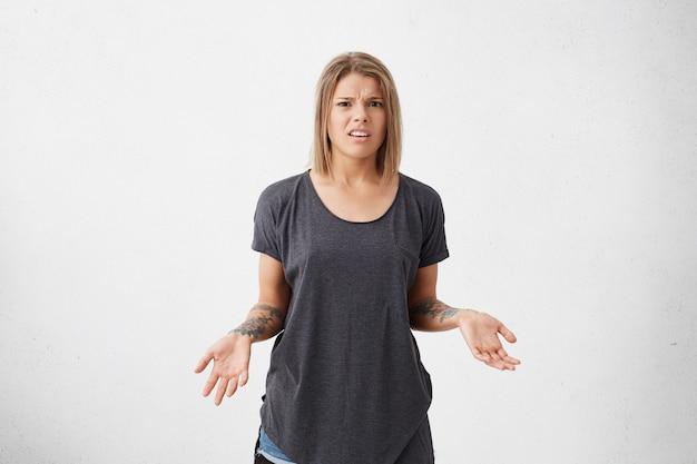 Раздраженная нахмуренная женщина с короткими крашеными волосами, одетая в свободную серую футболку, жестикулирует руками с татуировками в неуверенности и замешательстве. злая женщина позирует на белой стене Бесплатные Фотографии
