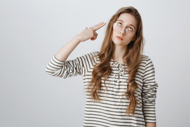 Раздраженная девушка закатывает глаза и стреляет из фальшивого пистолета, сходя с ума Бесплатные Фотографии