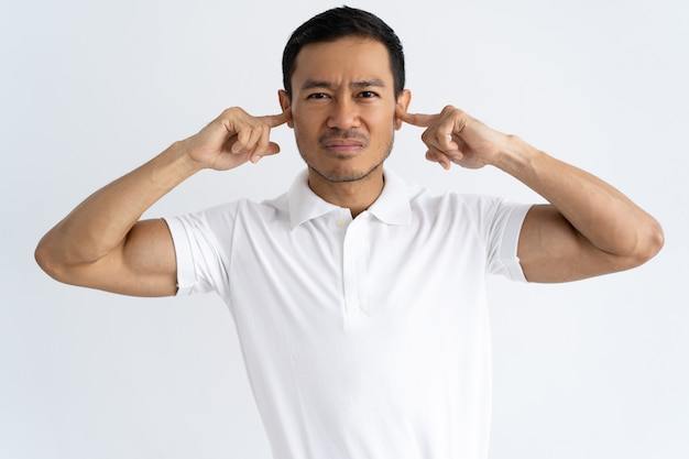 Annoyed guy tired of loud sounds Free Photo