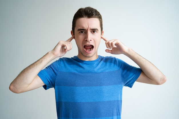 Annoyed man screaming and stopping ears with fingers Free Photo
