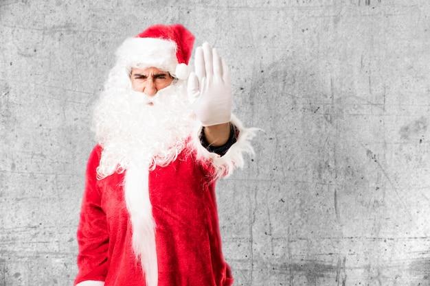 Annoyed man wearing santa claus costume Free Photo