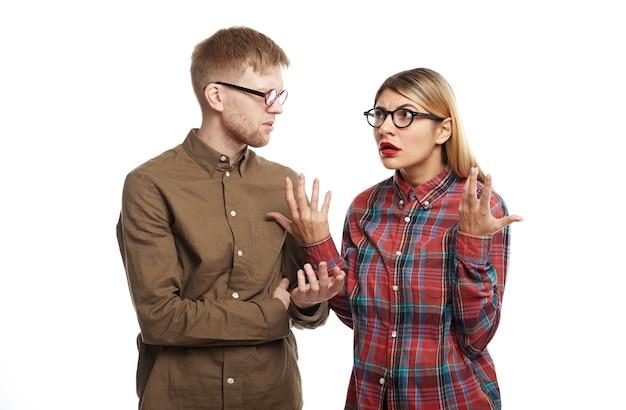 Раздраженная симпатичная девушка в кошачьих очках и клетчатой рубашке жестикулирует обеими руками, выражая возмущение, злясь на своего бестолкового парня, который снова забыл об их годовщине Бесплатные Фотографии