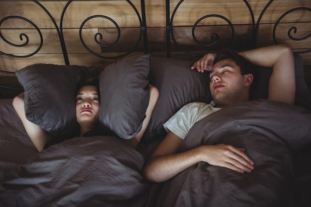 Donna infastidita che copre le orecchie con cuscini per bloccare il russare in camera da letto Foto Gratuite
