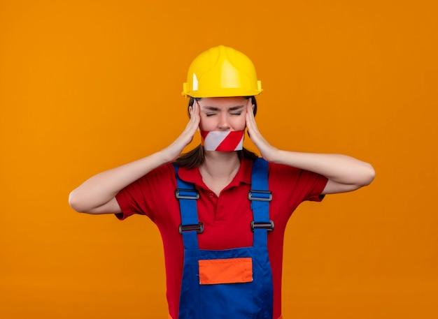 警告テープで密封されたイライラする若いビルダーの女の子の口は、孤立したオレンジ色の背景に両手で頭を保持します 無料写真