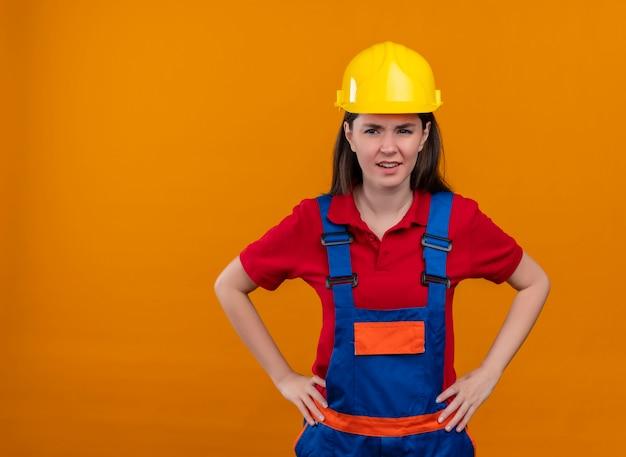 イライラする若いビルダーの女の子は、コピースペースで孤立したオレンジ色の背景に腰に両手を置きます 無料写真
