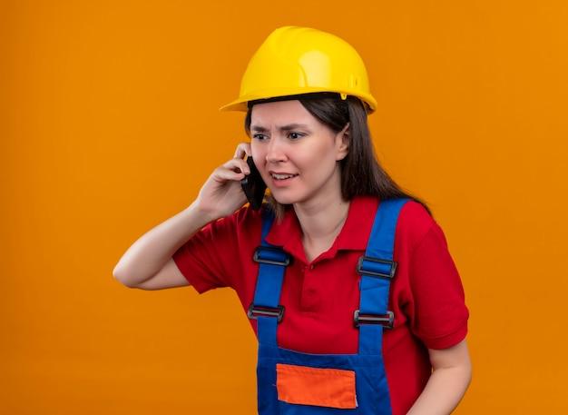 コピースペースと孤立したオレンジ色の背景で電話で話しているイライラする若いビルダーの女の子 無料写真