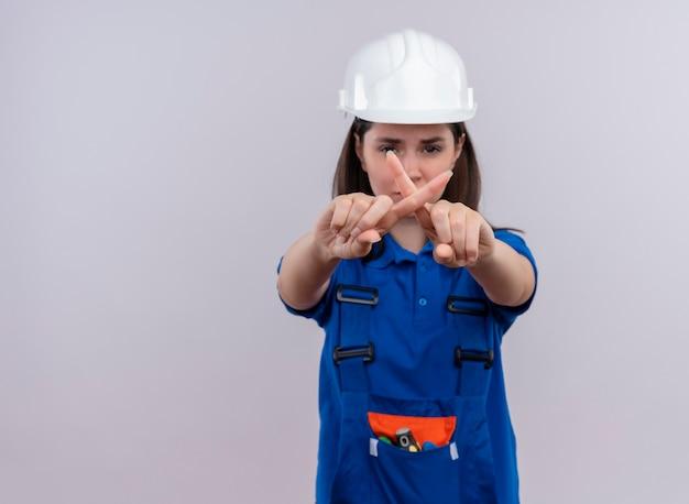 白い安全ヘルメットと青い制服のジェスチャーでイライラする若いビルダーの女の子は、コピースペースで孤立した白い背景に指でありません 無料写真