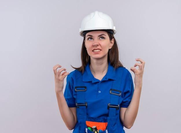 白い安全ヘルメットと青い制服を着たイライラした若いビルダーの女の子は手を上げて、コピースペースで孤立した白い背景を見上げます 無料写真