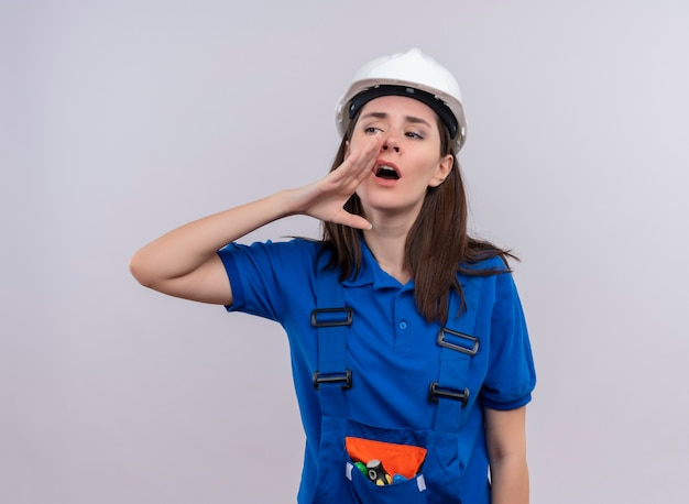 白い安全ヘルメットと青い制服を着たイライラした若いビルダーの女の子は、コピースペースで孤立した白い背景に誰かを呼び出すふりをします 無料写真