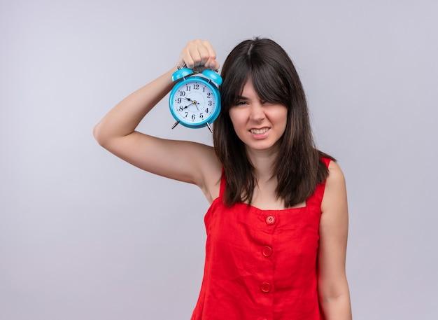 コピースペースと孤立した白い背景に手で時計を保持しているイライラする若い白人の女の子 無料写真