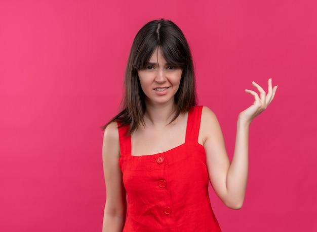 コピースペースと孤立したピンクの背景にカメラを見て空の手を保持しているイライラする若い白人の女の子 無料写真