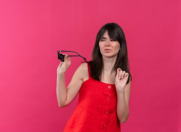 サングラスを保持し、孤立したピンクの背景で横を見てイライラする若い白人の女の子 無料写真