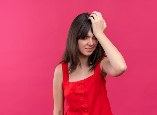 イライラする若い白人の女の子は、コピースペースで孤立したピンクの背景に頭を抱えています 無料写真
